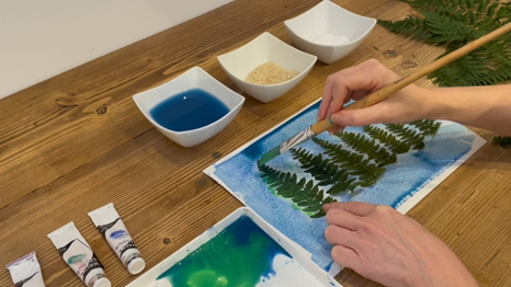 A hand with a paintbrush, painting a watercolour wash on top of leaves
