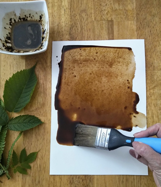 A piece of paper with a hand holding a large paintbrush creating a 'coffee wash'
